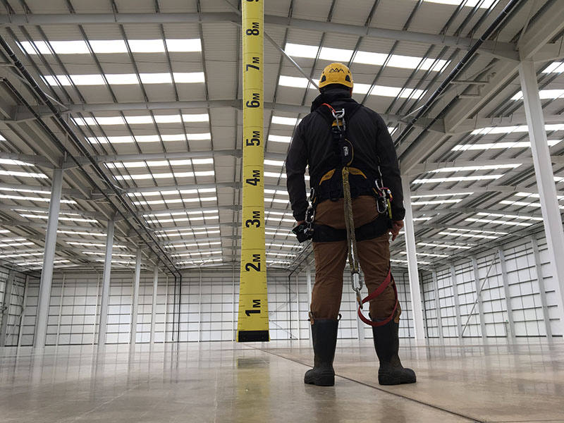 AAA worker looking at tape measure in large building.